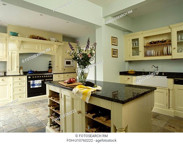 Island unit with wine storage in contemporary kitchen with cream fitted cupboards with black granite worktops