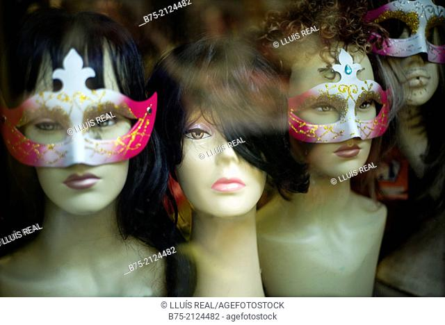 female mannequin heads with wigs and Venetian masks in the window of a hairdresser in Brixton, London, England, UK, Europe