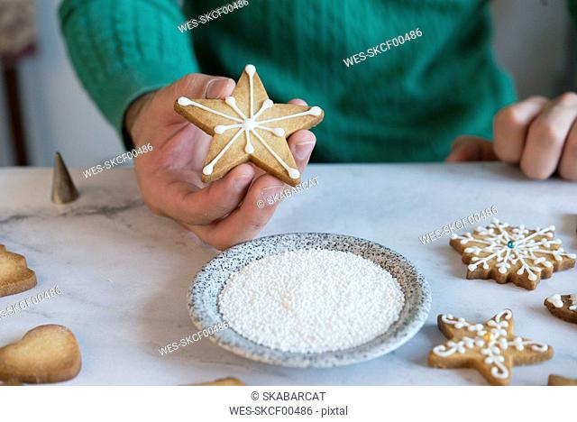 Man's hand holding Christmas Cookie, close-up