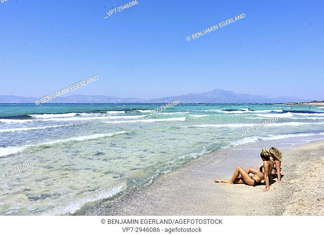 two young women, best friends, sitting together on the beach. Dutch ethnicity. At holiday destination Chrissi Island, Crete, Greece