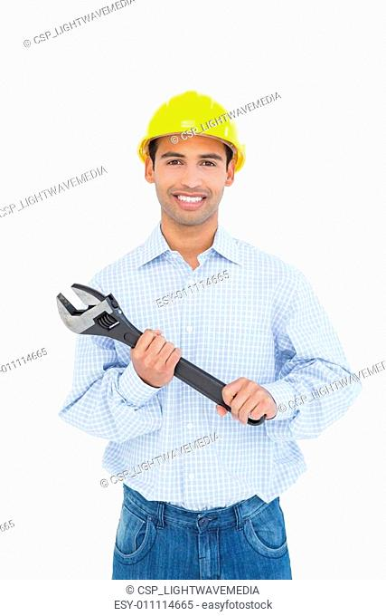 Portrait of a smiling young handyman holding a wrench
