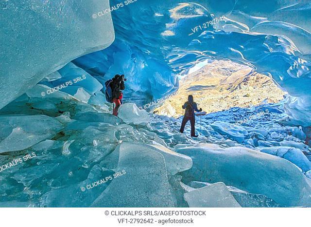 Hikers inside Forni Glacier Forni Valley Stelvio National Park Valfurva Valtellina Lombardy Italy Europe
