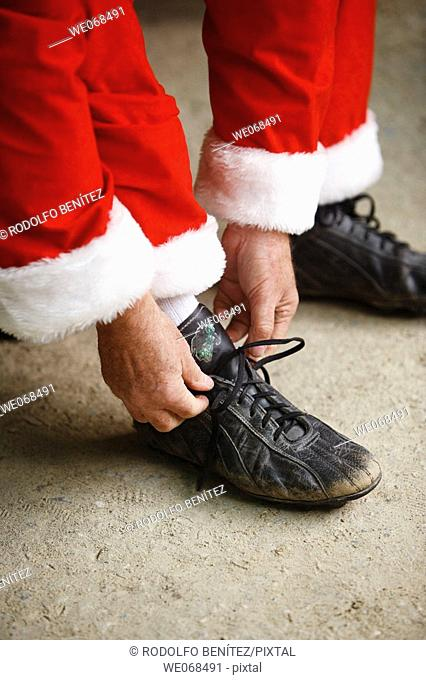 Santa putting on baseball shoes