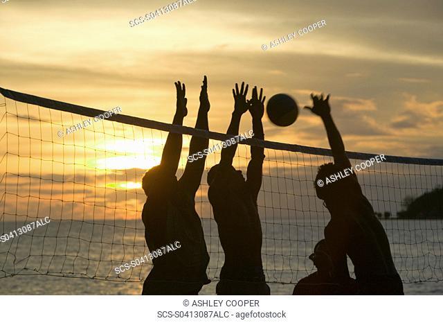 Fijian men playing beach volleyball at sunset at the Walu Beach Resort on Malolo Island off Fiji