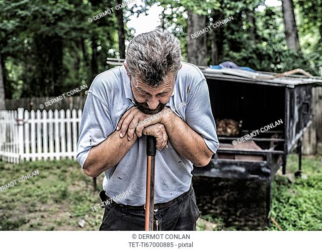 Man working by traditional Bosnian cook hut in backyard