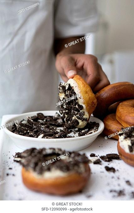 Doughnuts with white chocolate icing being dipped in crumbled Oreo biscuits