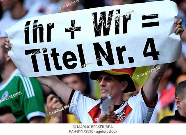 A German supporter holds a sign reading «you and us = title number four» the UEFA Euro 2016 Group C soccer match between Germany and Ukraine in Lille, France