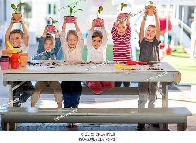 Girls and boys at preschool, portrait holding up pot plants at picnic table