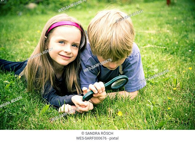 Brother and sister lying on meadow watching flower with magnifying glass