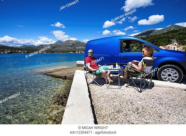 A couple sits outside their camper van at a beach along the coast; Slano, Croatia