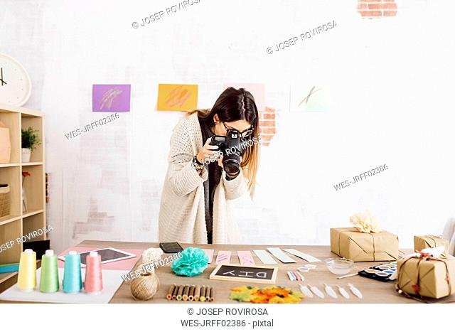 Young woman taking pictures with a camera for her craft blog