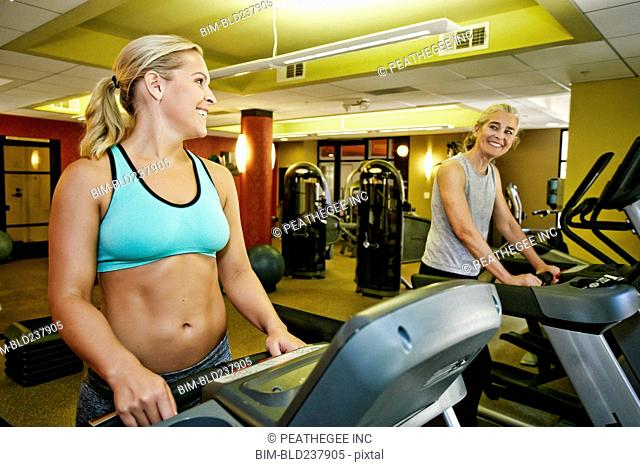 Smiling Caucasian mother and daughter on treadmills