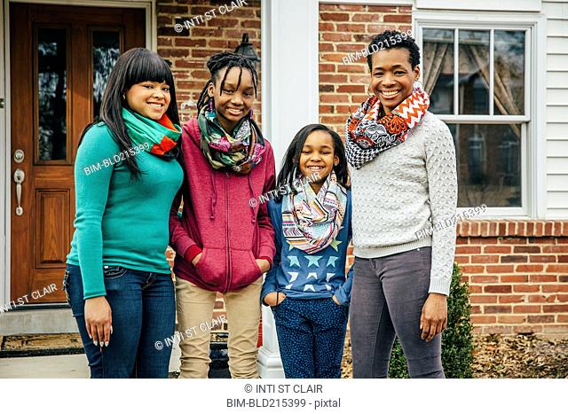 Black mother and daughters smiling outside house