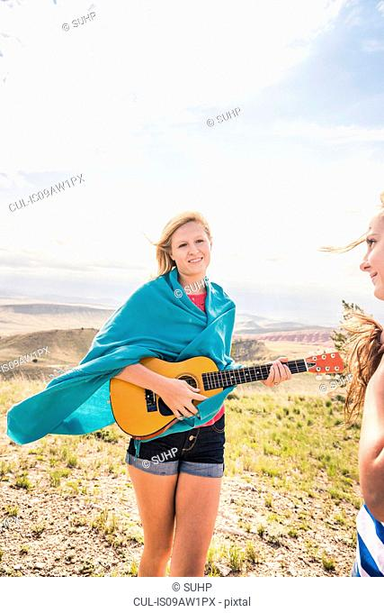 Teenage girl wrapped in blanket playing ukulele in hills, Bridger, Montana, USA