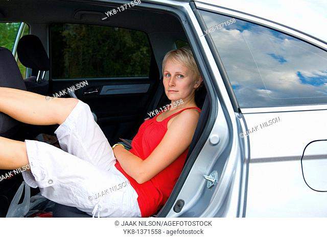 Young women sitting in car on road trip
