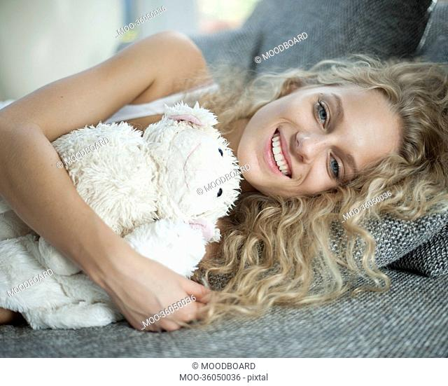 Portrait of young woman with teddy bear lying on sofa