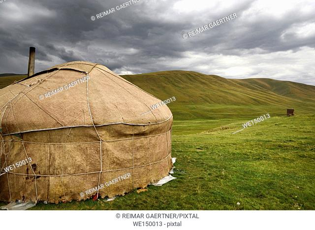 Yurt with chimney and outhouse in barren pastureland of Assy Plateau Kazakhstan