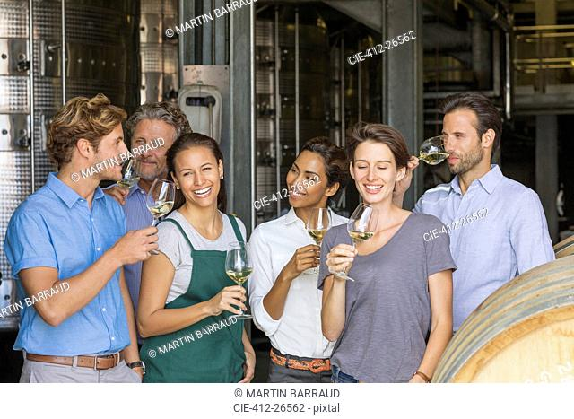 Winery employees tasting white wine in cellar