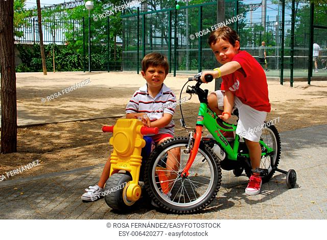 Two boys three and four years old with bikes playing in a public park, Madrid, Spain