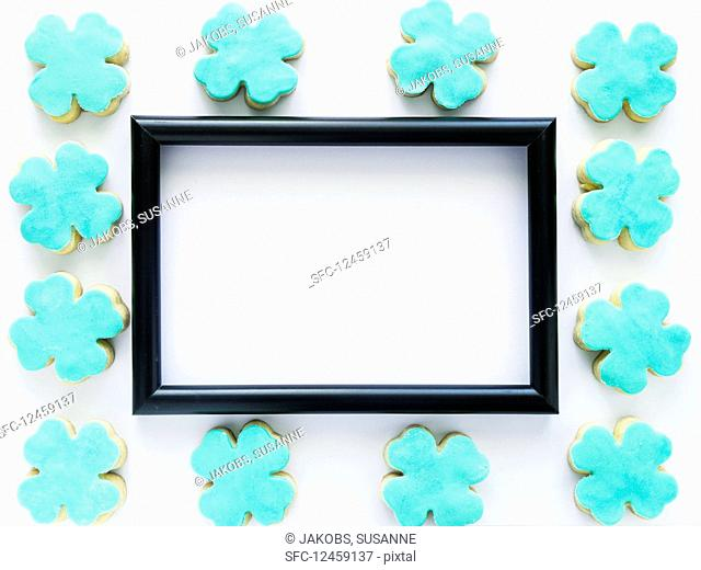 A black picture frame surrounded by clover-shaped cookies
