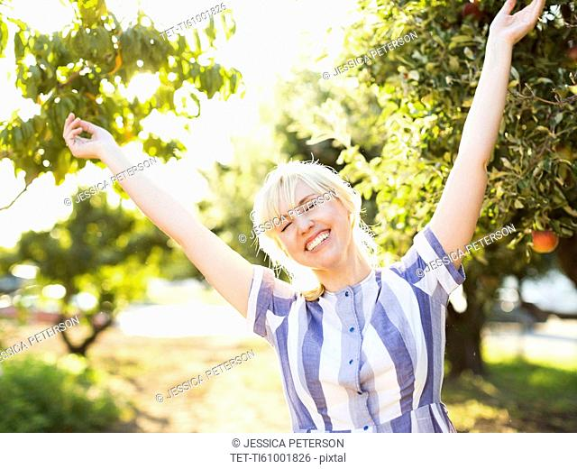 Portrait of blond woman in orchard
