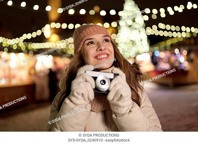 happy young woman with camera at christmas market