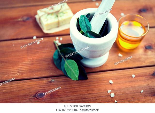 beauty, spa, body care, natural cosmetics and wellness concept - close up of mortar and pestle with leaves with leaves on wooden table