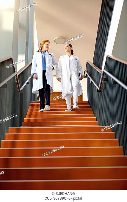 Two female doctors walking down steps, low angle view