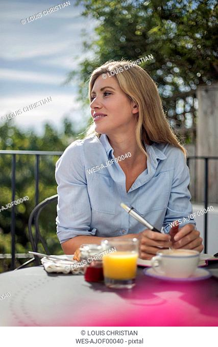 Portrait of woman, working at cafe table, outdoors