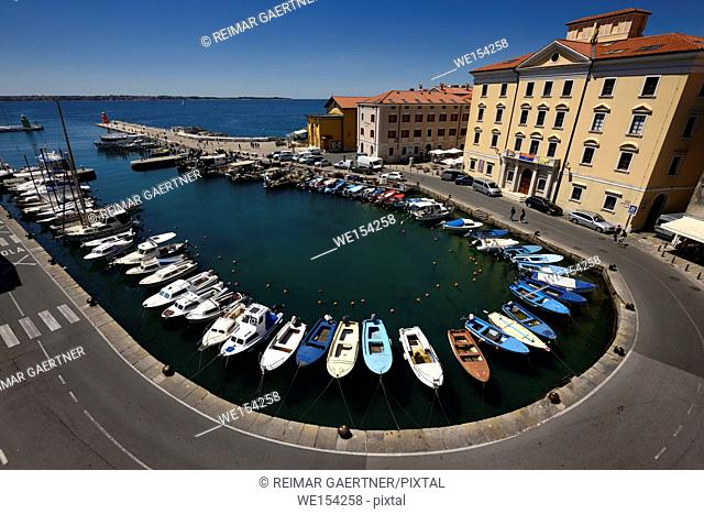 Horseshoe pattern of moored boats at the inner harbour of Piran Slovenia on the Adriatic Sea coast with blue sky