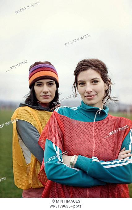 Portrait of two Caucasian women in sports clothing with team bibs of opposing teams and woolly hats side by side