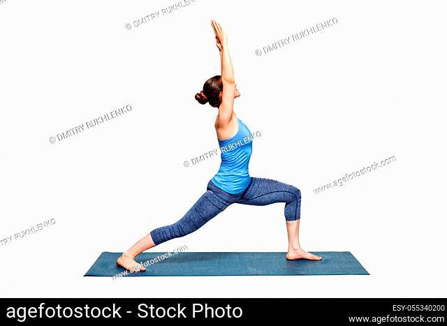 Beautiful sporty fit woman practices Ashtanga Vinyasa Yoga asana Virabhadrasana 1 - warrior pose 1 isolated on white