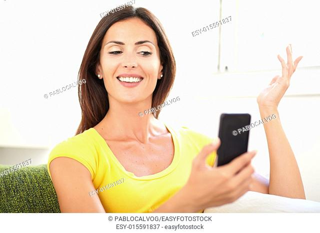 Caucasian woman using a mobile phone while holding her hand raised and smiling