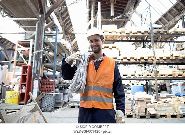 Smiling warehouseman in storehouse carrying tubes
