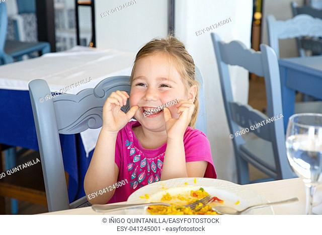 portrait of four years old blonde girl eating Spanish paella rice, laughing and looking at, sitting in restaurant