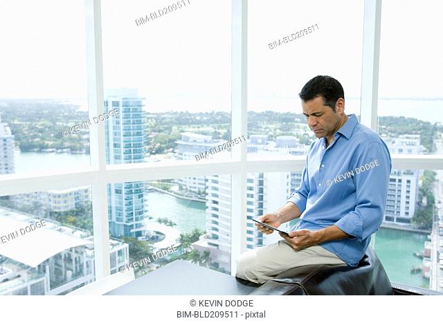 Hispanic businessman using digital tablet in office