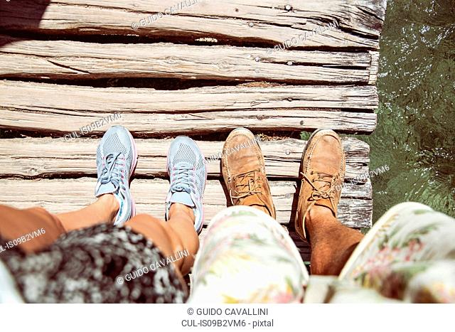 Personal perspective of couples feet standing on wooden bridge, Plitvice Lakes National Park, Croatia