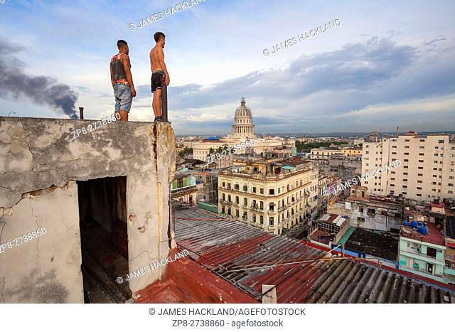 Two man admiring the view from a rooftop with El Capitolio visible in the distance in Central Havana, Cuba