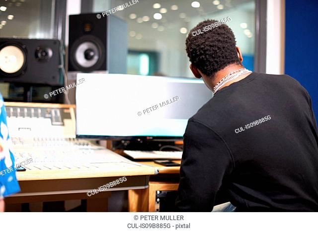 Rear view of young male college student at sound mixer in recording studio