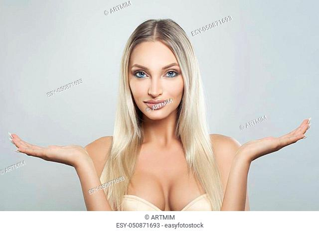 Attractive Spa Model Woman Showing Empty Copy Space on the Open Hands. Product Placement and Advertising Marketing Concept