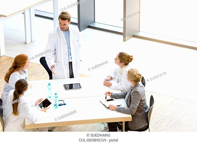 Group of doctors sitting at table, having meeting, elevated view