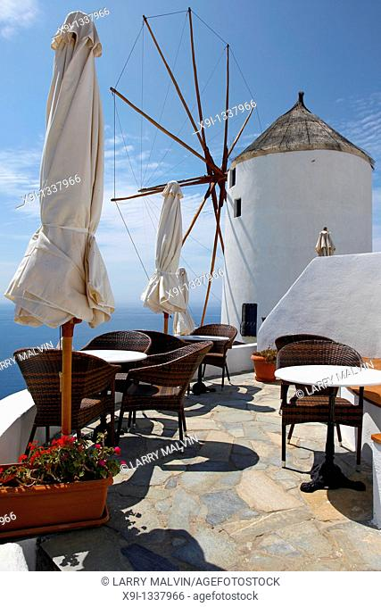 Restaurant on deck with windmill overlooking ocean in Santorini, Greece