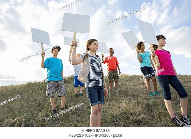 Schoolchildren holding blank billboards during field trip