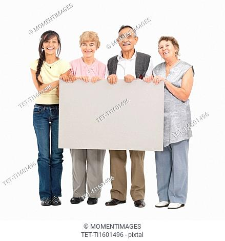Four people holding a blank poster