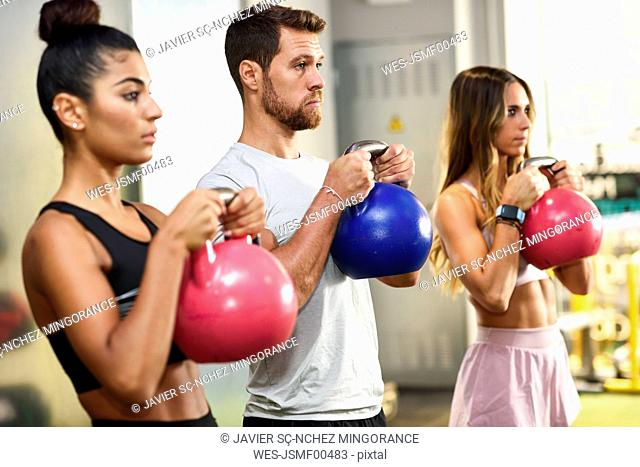 Young people doing kettle ball workout in a gym