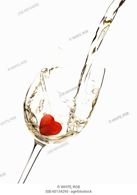 Pouring a glass of white wine with a heart-shaped ice cube