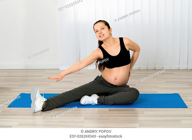 Pregnant Woman Stretching Her Leg On Exercise Mat
