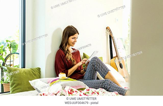 Relaxed young woman using digital tablet at home in bed