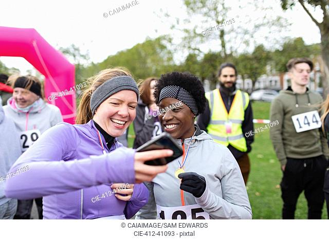 Female runner friends using smart phone at charity run in park