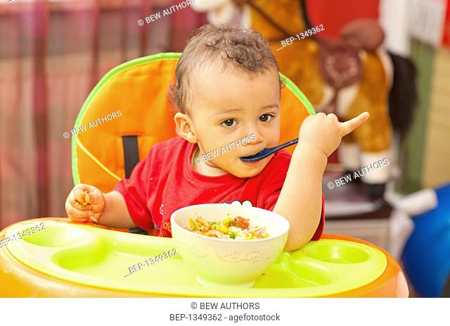 Adorable boy eating in baby chair